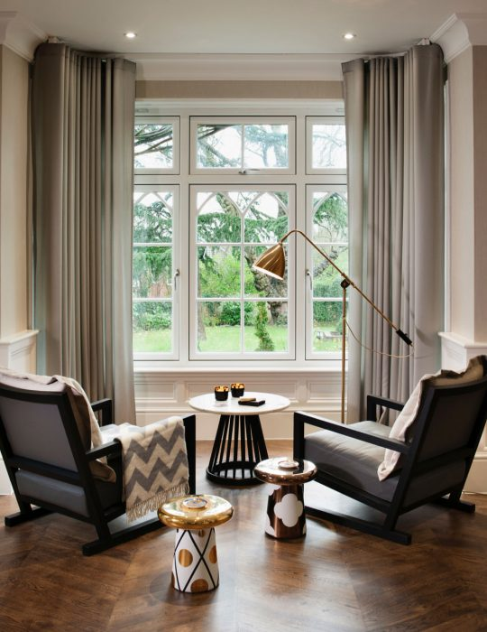 Two seats point to a large sash window in a traditional luxury sitting room design, North London