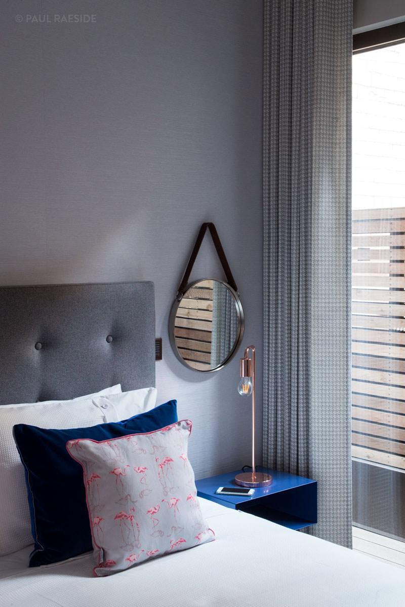 A stylish circular mirror hangs on the wall of luxury designed Soho Interior, London
