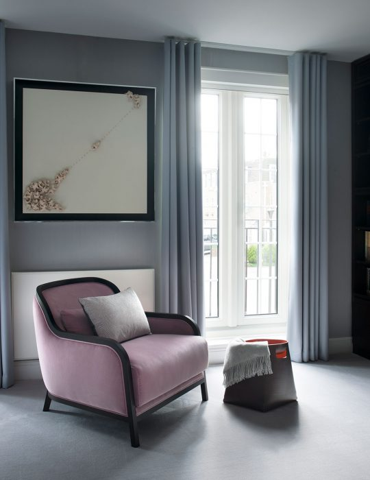 A comfortable seat sits in a designed sitting room.