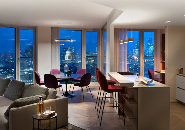 Views of the city from the interior of a luxury pied-à-terre, Southbank House, London. Stylish lighting illuminates the luxury interior overlooking St Pauls Cathedral at dusk.