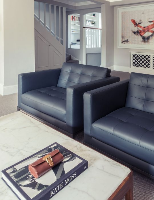 Two leather sits in a sitting room of interior designed lounge.