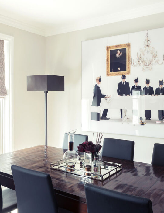 Art hangs above a dining table in a designed dining room interior