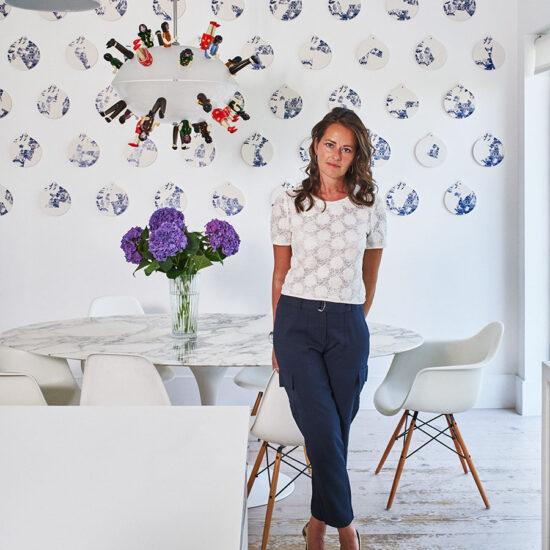 Simone Suss, founder of Studio Suss stands in a uniquely designed sitting room interior