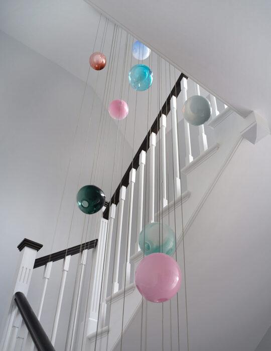 hanging art and staircase - Luxury sustainable interior design