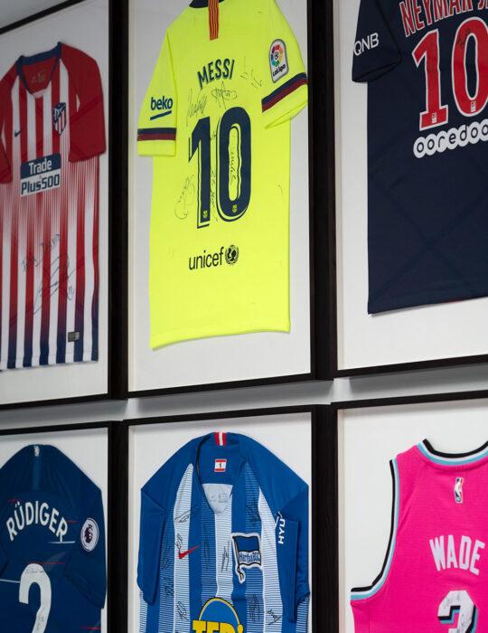 Neymar Messi framed football shirts in bedroom - Luxury sustainable interior design